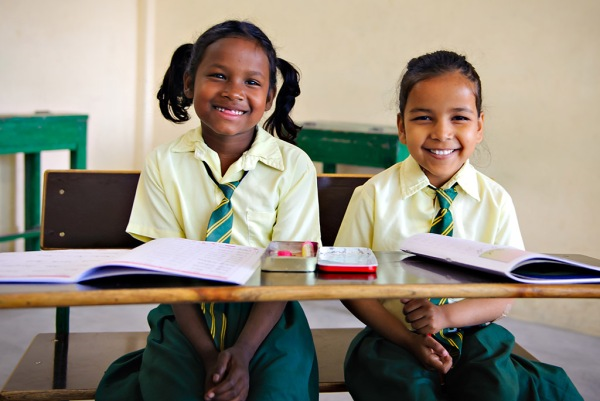 Santoshi & Cynthia sitting at one of the desks they will receive as part of the fundraising campaign.